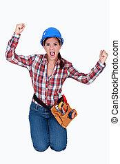 Triumphant female construction worker