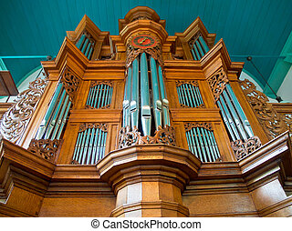 Wooden church organ against blue ceiling