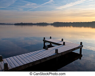 Jetty at lake in winter during sunrise