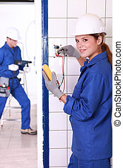 two skilled tradesman in blue jumpsuits working in housing...
