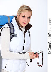 Blond woman with backpack and compass