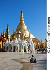 Shwedagon pagoda - A people sitting in front of Shwedagon...