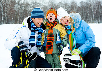 family going ice skating - happy young parents going ice...