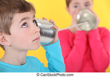 Two children communicating with tin can and string