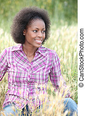 black woman sitting and relaxing in a field
