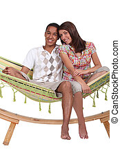 Happy couple sitting in a hammock