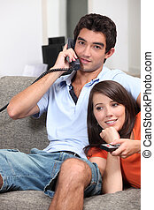 Young couple relaxing on the couch, talking on the telephone...