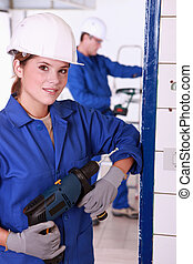 Young female electrician with a power drill