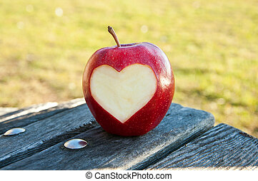 Lonely apple with carved heart on the bench