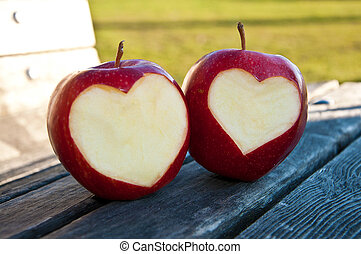 apples with hearts on the bench in park
