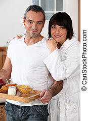 a man bringing breakfast on a platter and his wife wearing a bathrobe