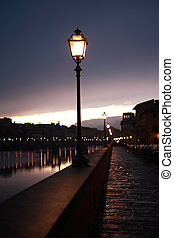 Street Lamps Near River - Night in Florence. Glowing vintage...
