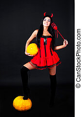 imp with pumpkins - sexy young brunette woman dressed as an...