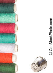 spools of thread and thimble for sewing on white background