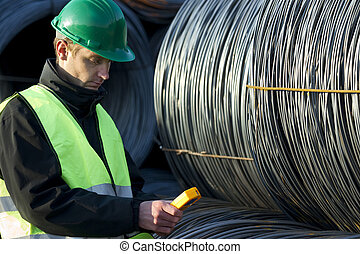 Supervisor Looking At Geiger Counter With Cable Wire Rolls -...