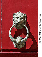 Bronze lion door knocker on red door in Mdina, Malta.