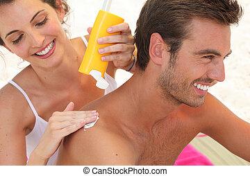 Couple applying suncream