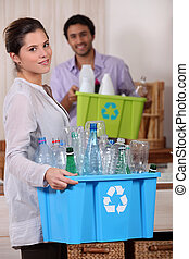 Young couple at home holding crates of plastic bottles