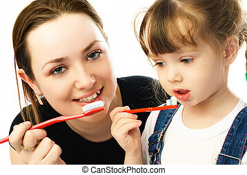 mother and daughter brushing teeth - beautiful young mother...