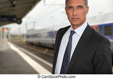 portrait of a businessman at train station