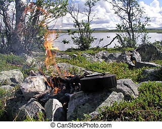 Camp fire by the lake