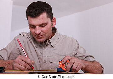 Tradesman marking a measurement with a pencil