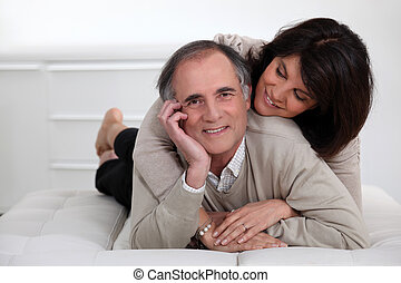 mature couple lying in bed showing their affection