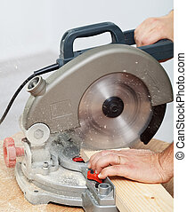 Worker hands cutting wooden plank with electric circular saw...