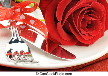 Red rose and cutlery on white plate - Closeup of red rose...
