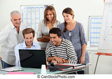 Co-workers gathered around computer screen