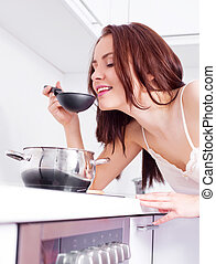 woman cooking - beautiful young woman cooking dinner in the...
