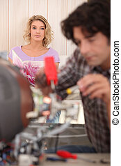 Woman looking at her partner while he fixes an object