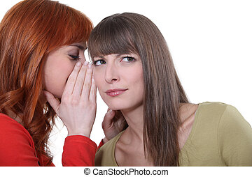 Woman whispering into her friends ear