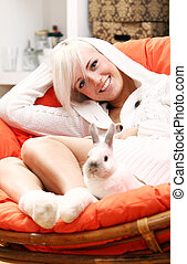 Cute blonde girl sitting in the chair with bunny - Young and...
