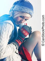 Girl in warm clothing is holding a cup of hot drink -...