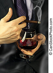 Old Brandy Glass at male hand, smoking cigar - Old Brandy...