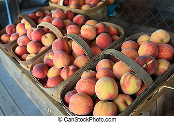 Peaches at the outdoor market in wooden baskets. - South...