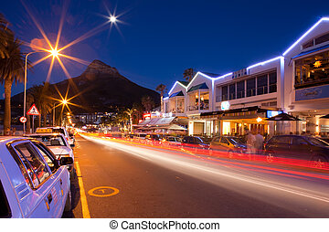 Night shot of Capms Bay street with Mountains. - Car lights...