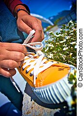 Fresh Kicks Tying Laces - Close up of person tying orange...
