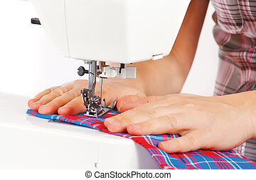 Hands of a seamstress at the sewing machine on a white...