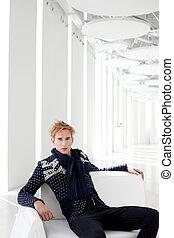 modern blond male futuristic sci-fi sitting in white indoor