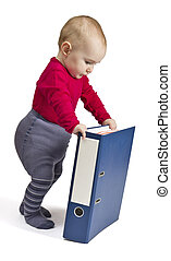 small child standing next to blue ring binder - small child...