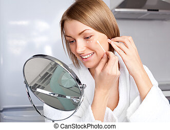 woman applying cream - beautiful young woman applying cream...