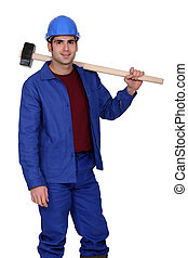 Construction worker holding a large mallet hammer