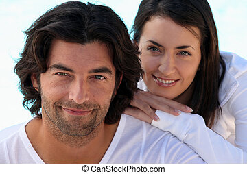 Head and shoulders shot of a well matched couple in white