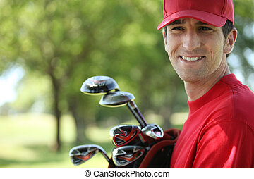 Golfer holding golf clubs smiling.