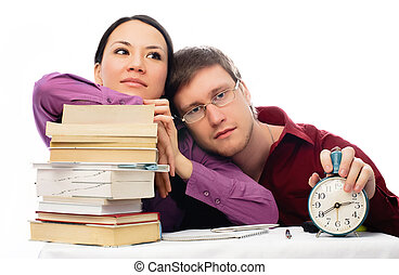 two lazy students sitting by the table with a lot of books...