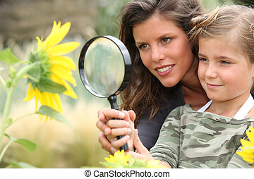 Young mum and daughter looking at a sunflower through a...