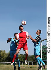 3 young men playing soccer