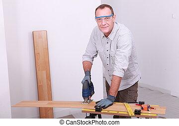 Man cutting floorboard